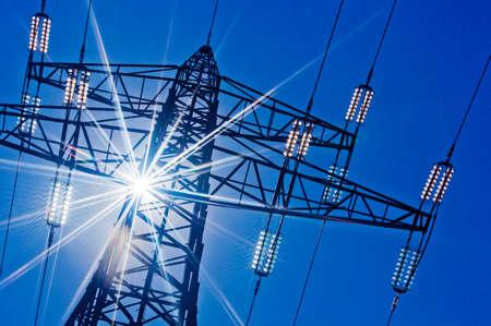 ein Hochspannungsmasten für Strom gegen den blauen Himmel und Sonnenstrahlen
