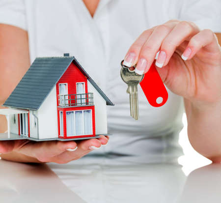 house for rent: a broker for real estate with a house and a key. rent and house sale by real estate agents.