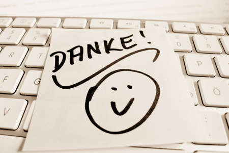 grateful: a sticky note is on the keyboard of a computer as a reminder: thank you Stock Photo