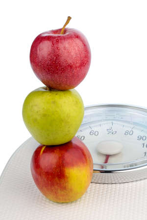 medizin: several apples on a balance for people. symbolic photo for diet and healthy, vitamin-rich diet.