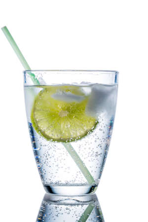 carbonic: a glass of fresh drinking water and a lime. mineral water as a thirst quencher. Stock Photo