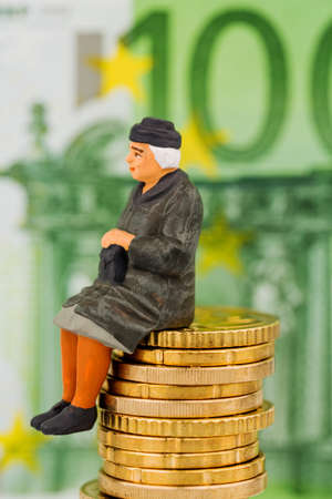oldage: pensioner sitting on money stack, symbol photo for pension, retirement, old-age security