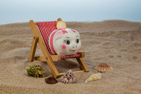 last minute: beach chair with euro currency on the sandy beach. symbolic photo for travel costs, holidays, vacations. save on holiday