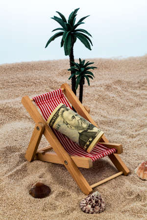 deck chair with dollars on the sandy beach. symbolic photo for travel costs, holidays, vacations. save on holiday photo