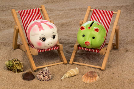 deck chair with piggy bank on the sandy beach. symbolic photo for travel costs, holidays, vacations. save on holiday photo