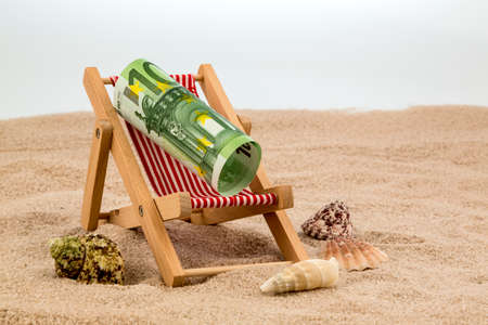 a deck chair with a euro banknote. symbolic photo for saving on holiday and when traveling photo