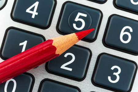budget crisis: a red pen is on a calculator. save on costs, expenses and budget for bad economy Stock Photo