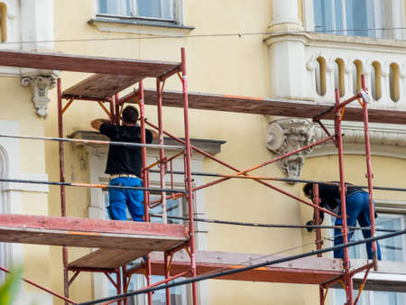 scaffold: construction workers build a scaffolding at a construction site