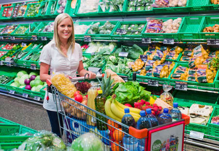 cheaper: a young woman shopping in the supermarket  full shopping cart