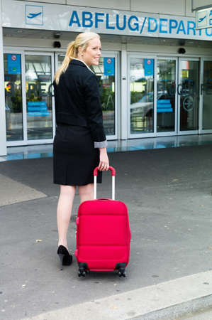 a young businesswoman with suitcase at an airport  photo
