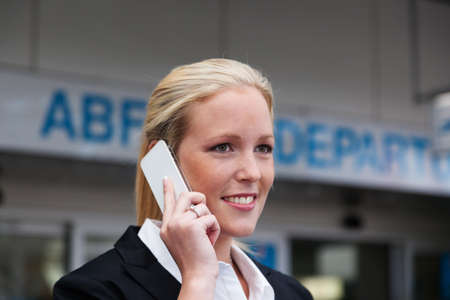 abroad: a business woman on the phone with her cell phone at the airport  roaminggebürhen in smartphones abroad Stock Photo