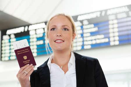 vrouw met paspoort en vliegtickets op een luchthaven te wachten op haar vertrek op vakantie Stockfoto