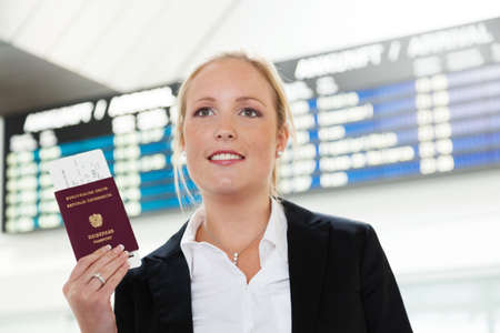 woman with passport and airline tickets at an airport waiting for her departure on holiday  版權商用圖片