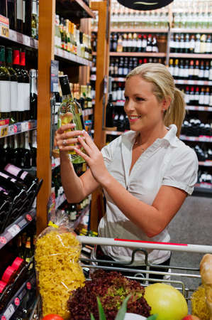 local supply: a woman buying wine in a supermarket  wine rack with wines from around the world  Stock Photo