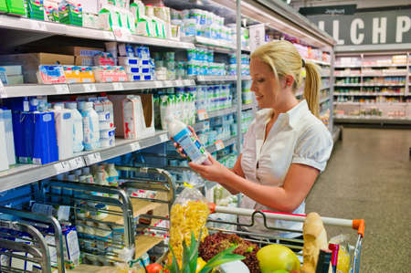 refrigerated: a young woman buying milk at the grocery store  standing in front of the refrigerated section  Stock Photo