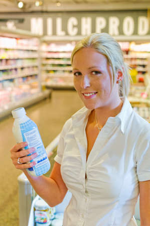 grocers: a young woman buying milk at the grocery store  standing in front of the refrigerated section  Stock Photo