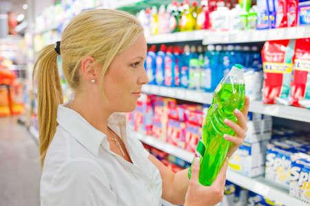 een vrouw koopt schoonmaakproducten bij een supermarkt plank met reinigingsmiddelen Stockfoto