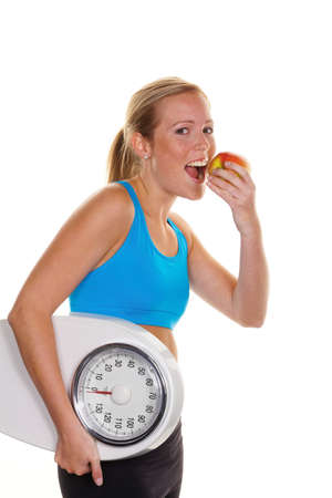 young woman with bathroom scale and apple  successful diet photo