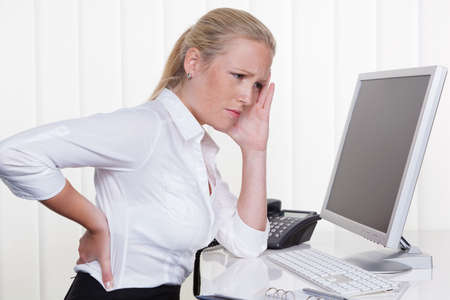 a woman sitting in office front of her computer and has back pain