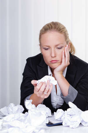 a woman in the office with crumpled paper  anger, stress and frustration in the workplace