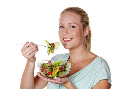 eat right: a young woman eating a crisp salad in the lunch break  healthy diet with vitamins