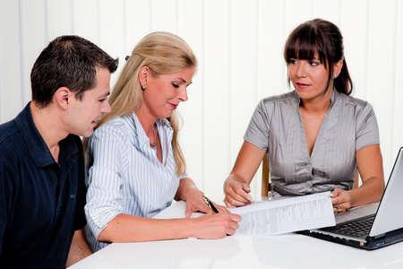 contrato de trabajo: mujer joven firma un contrato en una oficina