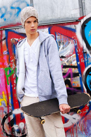 a cool-looking teenager man in front of graffiti photo
