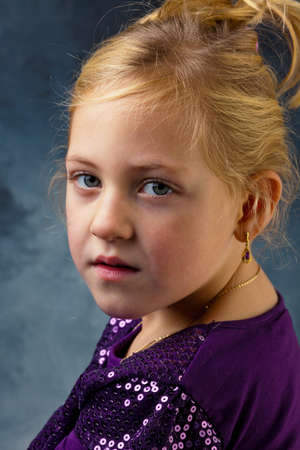 the portrait of a little girl against a gray background  Stock Photo