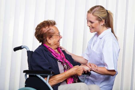 een verpleegkundige en een oude vrouw in een rolstoel Stockfoto