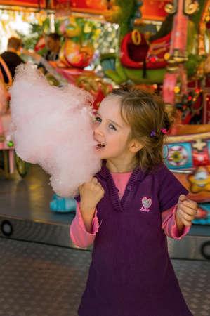 een meisje heeft plezier en ik kijk naar een kermis en eet suikerspin Stockfoto