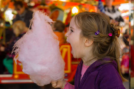 fairground: a little girl on a kirtag with cotton candy  fun and joy of fair