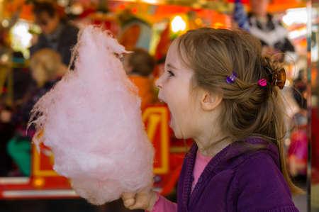 una niña en un Kirtag con la diversión de algodón de azúcar y la alegría del justo