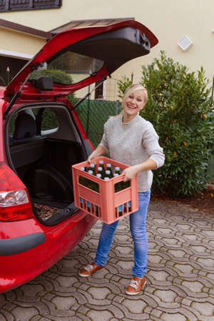 ergonomics: a young woman lifts a crate of bottles from their car  real life prevents back pain and herniated disc