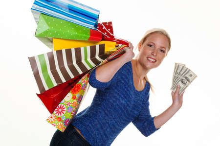 behavior: a young woman with colorful shopping bags while shopping  with dollar banknotes