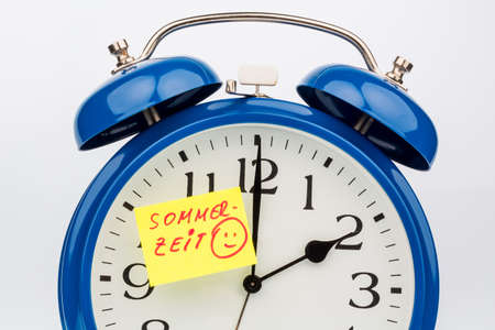 an alarm clock with a note as a reminder to the uhrumstellung at summer time photo