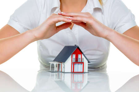 homeowners insurance: house is protected  woman holding hands over model house