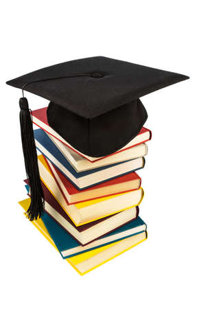 a mortarboard on a book stack, symbol photo for education and skills photo