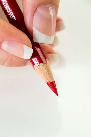 cut price: a hand holding a red pen  symbolic photo for savings and budegt cuts