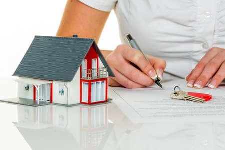 een vrouw tekent een contract om een huis te kopen met een makelaar