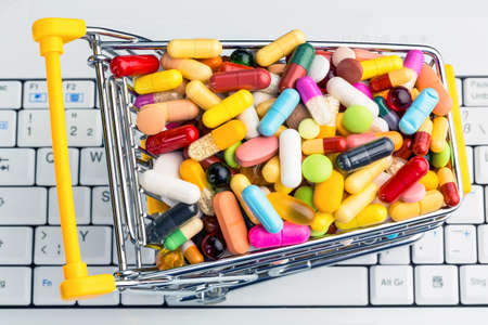 consumerist: tablets with shopping cart  symbolic photo for the purchase of medicines on the internet Stock Photo