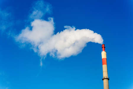 emission: chimney of an industrial company with smoke  symbolic photo for environmental protection and ozone