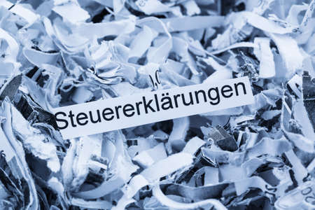tax aligned: shredded paper tagged with tax returns, symbol photo for tax burden and retention requirements