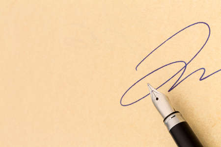 Leasing: a signature and a fountain pen on yellow paper  symbolic photo for contract testament and graphology Stock Photo
