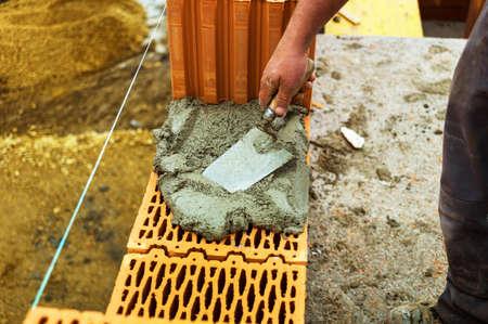 single familiy: trabajador de la construcci�n an�nimo en un sitio de construcci�n al edificar una casa construy� un muro de ladrillos de la pared de ladrillo de un icono de imagen casa s�lida para el trabajo no declarado y la torpeza