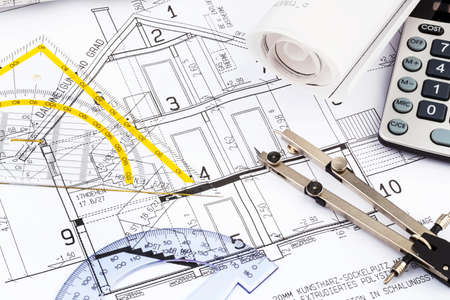 an architect s blueprint with a calculator  symbolic photo for funding and planning of a new house