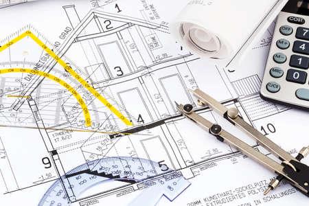 een architect s blauwdruk met een rekenmachine symbolische foto voor de financiering en de planning van een nieuwe woning