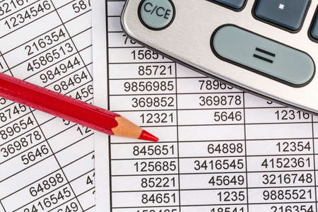 calculation: a calculator is on a balance sheet figures are statistics. photo icon for sales, profit and cost.