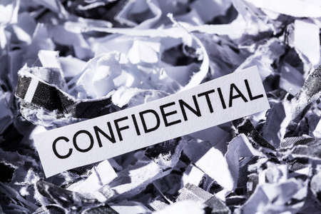 shredded paper tagged confidential, symbol photo for data destruction, banking secrecy and confidentiality 版權商用圖片