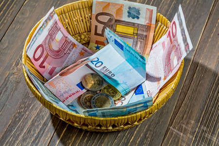 contributions: a basket of money for donations and gratuities