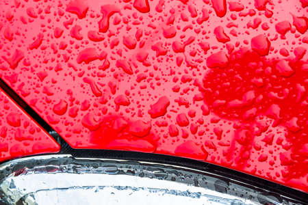 weather protection: after a rain, droplets of rain on top of the paint of a car. water drops on red